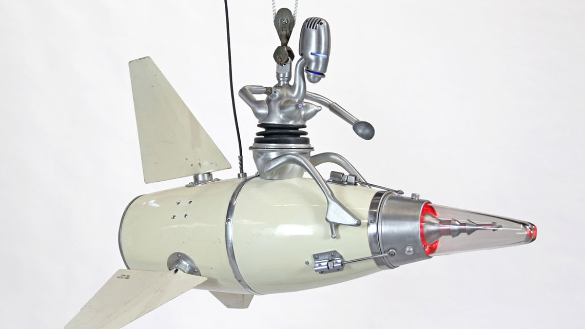 Kinetic sculpture of female robot riding on a rocket.